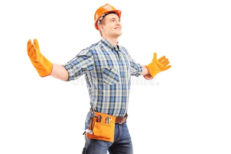 Lycklig manuell arbetare med fördelande armar för hjälm royaltyfri fotografi
