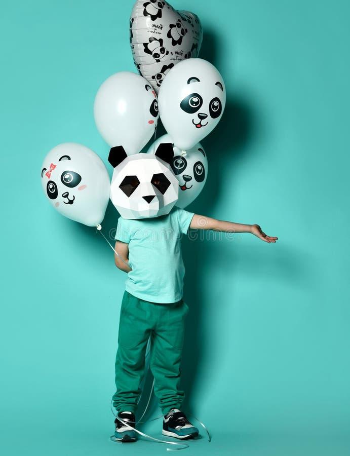 Lycklig maskeringspojke för liten panda med gruppen av ballonger för födelsedagparti med utrymme för fri text på gräsplan royaltyfri foto