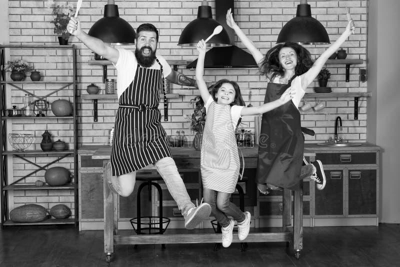 Lycklig matlagning Moder och fader med lilla flickan Liten flicka med f?r?ldrar i f?rkl?de Familjdag Fader moder och arkivfoto