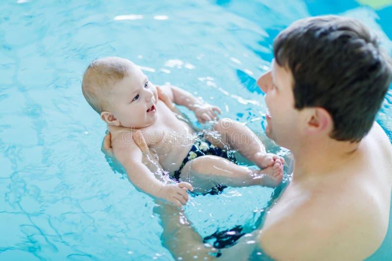 Lycklig medelålders fadersimning med gulligt förtjusande behandla som ett barn i simbassäng Le farsan och det lilla barnet, nyföd arkivfoto