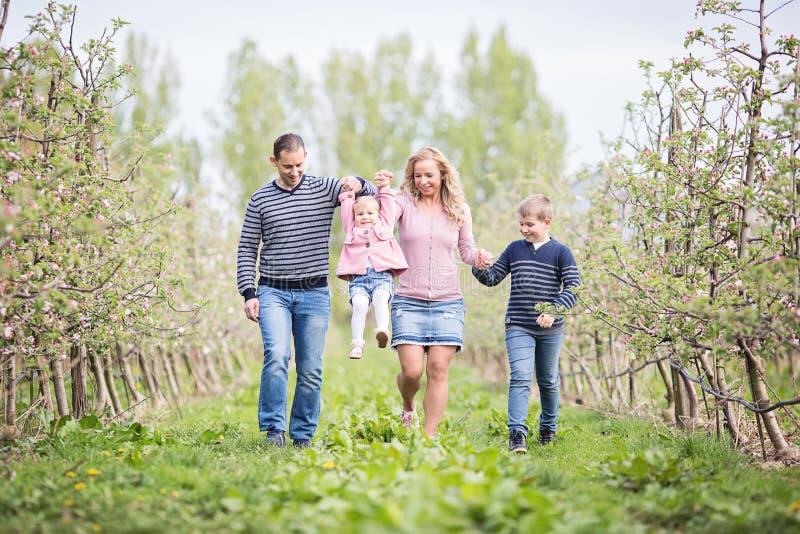 Lycklig medlemfamilj för barn som fyra tillsammans utomhus går i späckhuggare arkivfoton