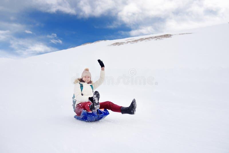 Lycklig mellersta ålderkvinna som har gyckel under rullande down berglutningen på släden i fjällängar arkivfoton