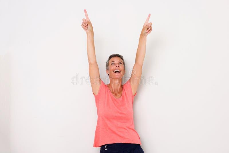 Lycklig mellersta ålderkvinna som skrattar med lyftta armar och pekar upp fingrar arkivfoton