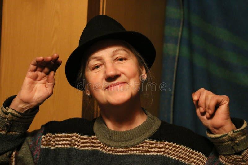 Lycklig mellersta åldrig kvinna i svart hatt arkivfoto