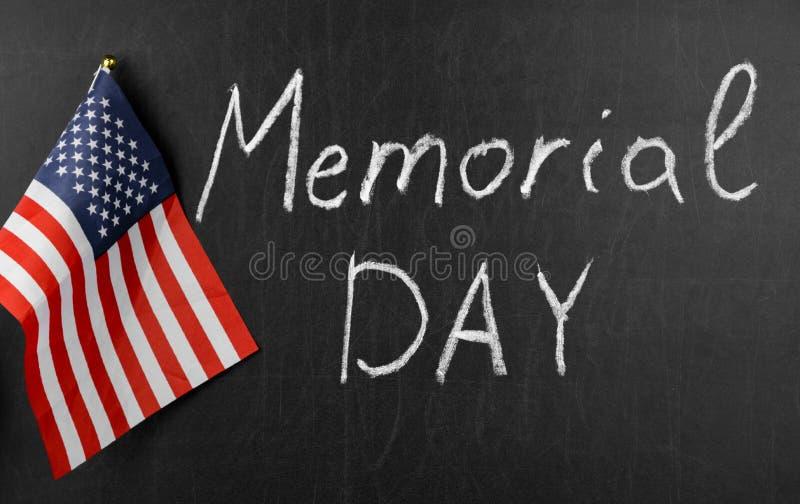Lycklig Memorial Day f?r ` som ` ?r skriftlig p? en svart tavla bredvid amerikanska flaggan arkivbilder