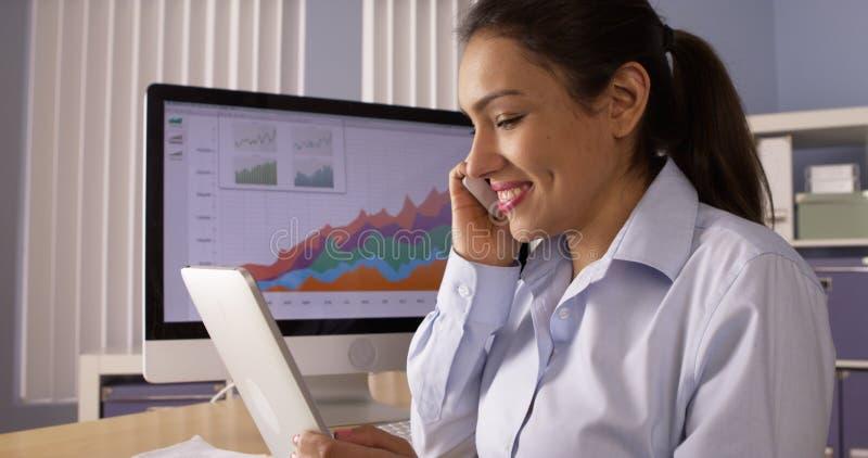 Lycklig mexicansk affärskvinna som arbetar på skrivbordet arkivbilder
