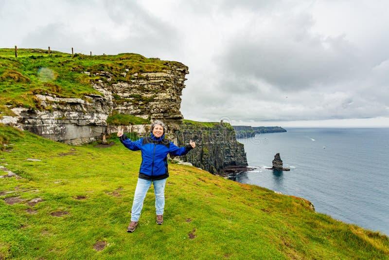 Lycklig mexicansk mogen kvinna på klipporna av Moher med den Branaunmore havsbunten i bakgrunden royaltyfri bild