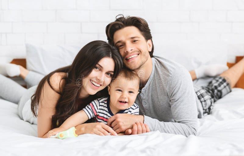 Lycklig millennial familjbindning på säng med behandla som ett barn royaltyfria foton