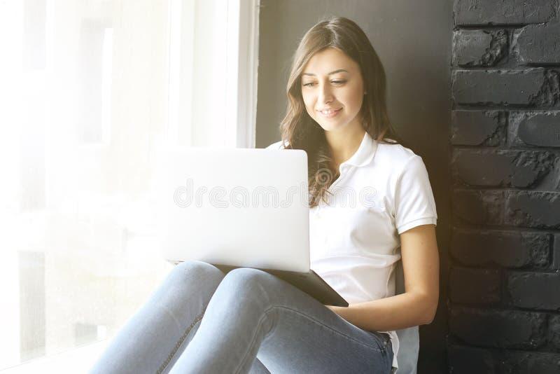Lycklig millennial flicka med bärbara datorn på fönsterbräda Stående av den unga kvinnan med diastemamellanrum mellan tänder härl royaltyfria foton