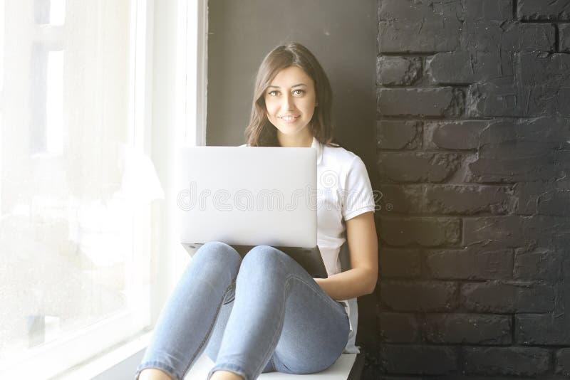 Lycklig millennial flicka med bärbara datorn på fönsterbräda Stående av den unga kvinnan med diastemamellanrum mellan tänder härl royaltyfria bilder