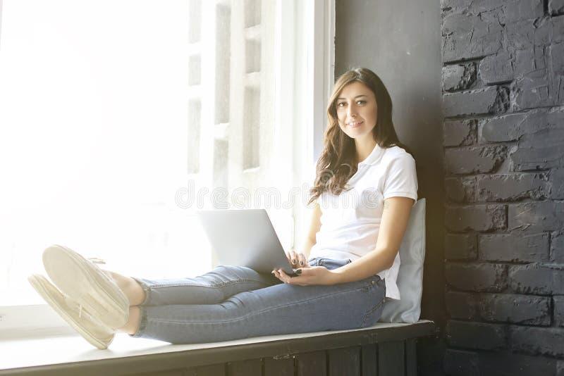 Lycklig millennial flicka med bärbara datorn på fönsterbräda Stående av den unga kvinnan med diastemamellanrum mellan tänder härl royaltyfri bild