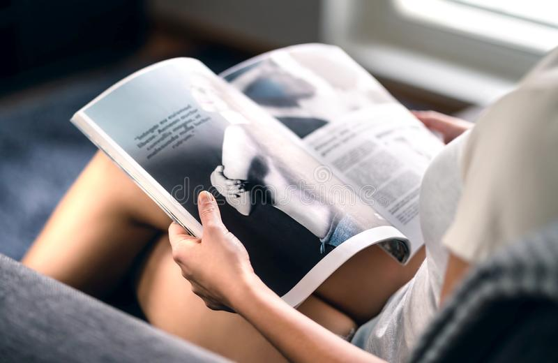 Lycklig millennial tidskrift för damläsningmode med senast skönhettrend- eller kändisnyheterna- och intervjuartiklar royaltyfri fotografi