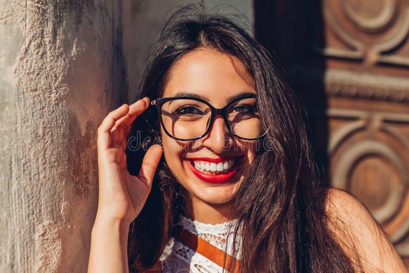 Lycklig mitt-östlig högskolaflicka som ler och ser kameran Utomhus- stående av bärande exponeringsglas för ung kvinna fotografering för bildbyråer