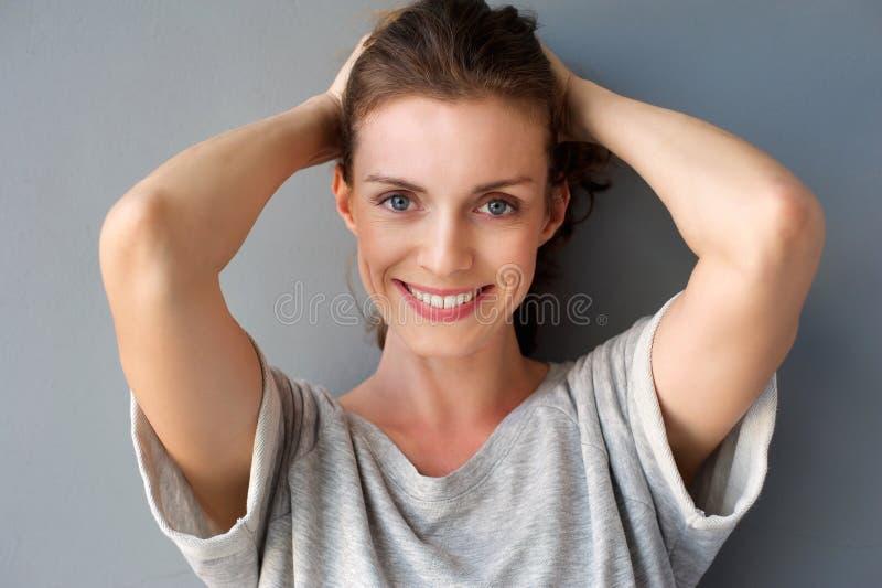 Lycklig mitt- vuxen kvinna som ler med händer i hår royaltyfri fotografi