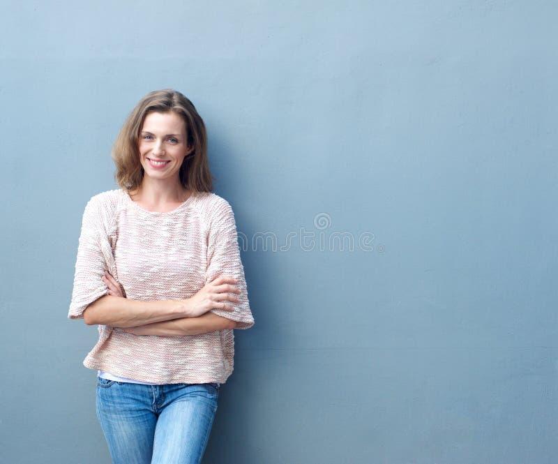 Lycklig mitt- vuxen kvinna som ler med korsade armar royaltyfri fotografi