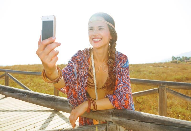 Lycklig modebohoflicka utomhus med smartphonen som tar selfie arkivfoton
