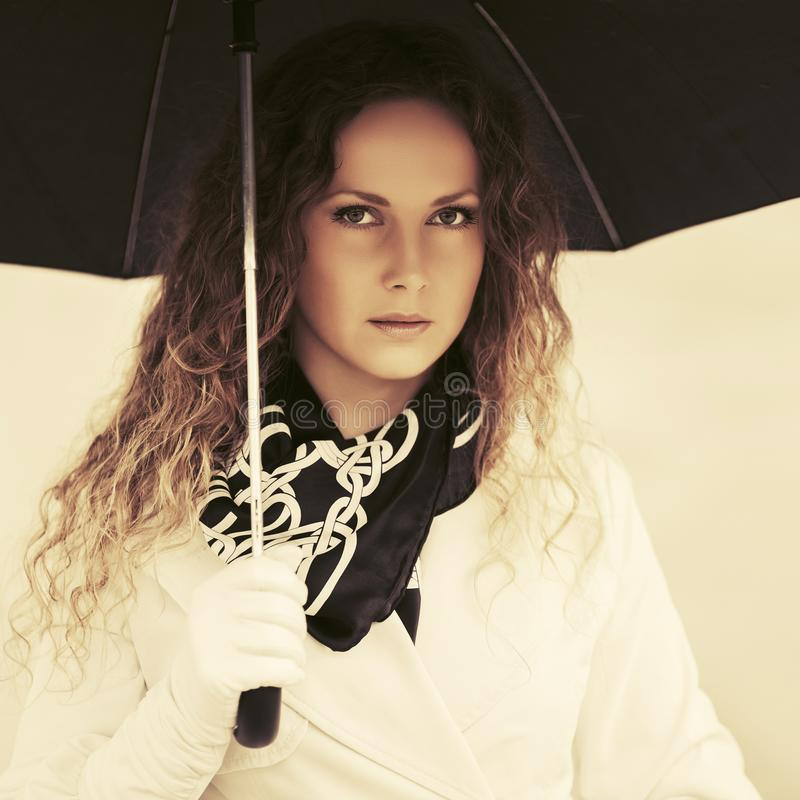 Lycklig modekvinna i det vita dikelaget med paraplyet arkivbilder