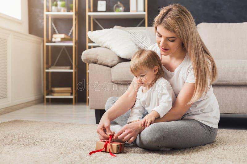 Lycklig moderöppningsgåva med hennes dotter royaltyfri foto