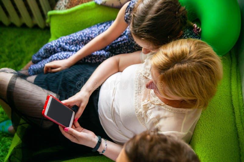 Lycklig moder, fader och liten flicka med smartphonen i säng hemma royaltyfria bilder