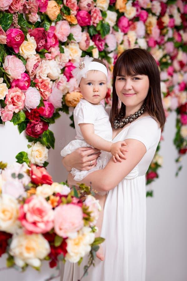 Lycklig moder med den lilla dottern över blommaväggen royaltyfria bilder