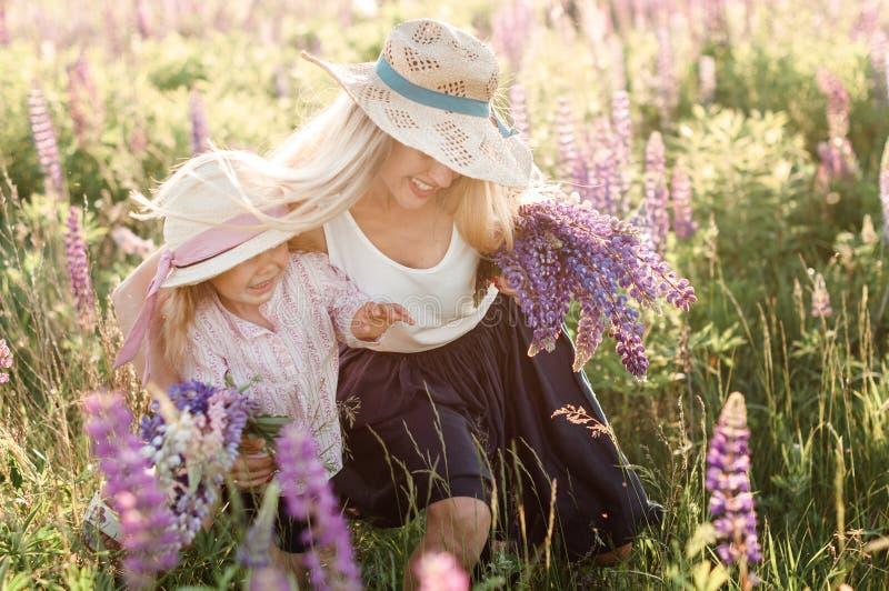 Lycklig moder med den lilla dottern i sugrörhattar med en bukett av lupine blommor royaltyfria bilder