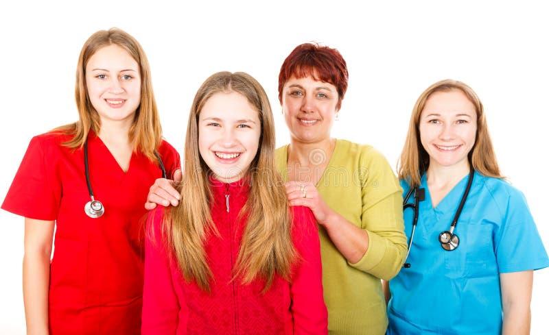 Lycklig moder med dottern och de unga kvinnligdoktorerna royaltyfri foto