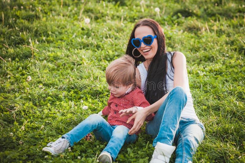 Lycklig moder med hennes lilla son som sitter på gräs i sommardag royaltyfria foton