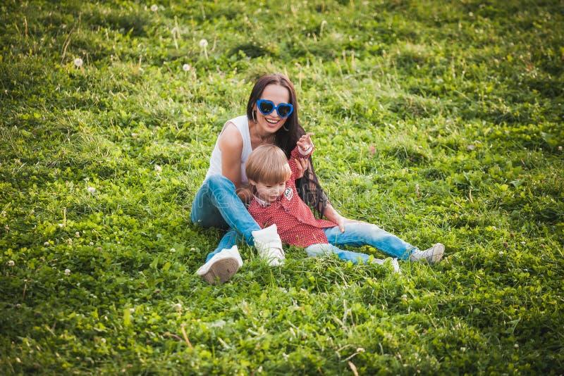 Lycklig moder med hennes lilla son som sitter på gräs i sommardag fotografering för bildbyråer