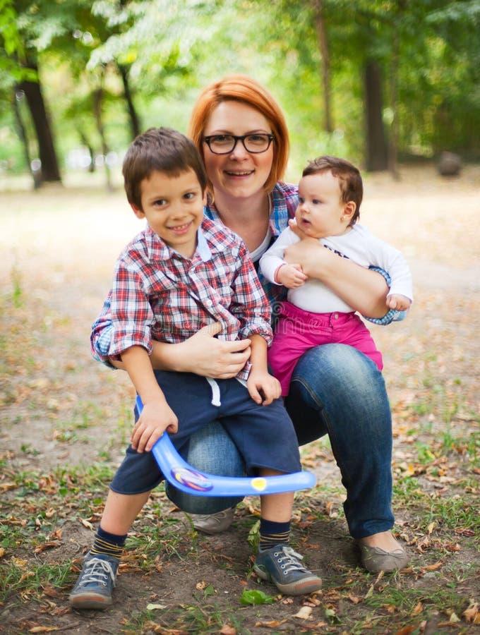 Lycklig moder med två barn royaltyfria bilder