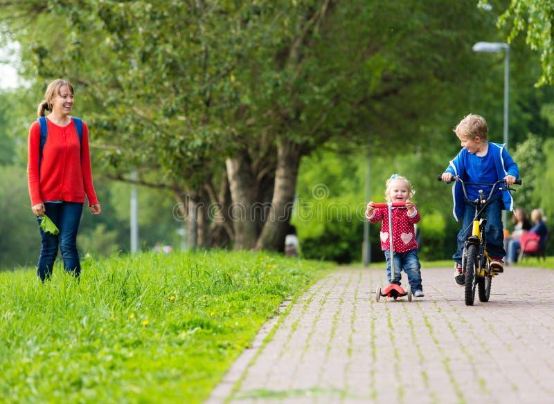 Lycklig moder med två ungar på sparkcykeln och cykeln in royaltyfri fotografi