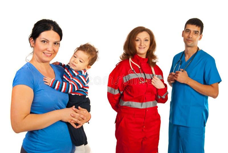 Lycklig moder med ungen och doktorer arkivbild