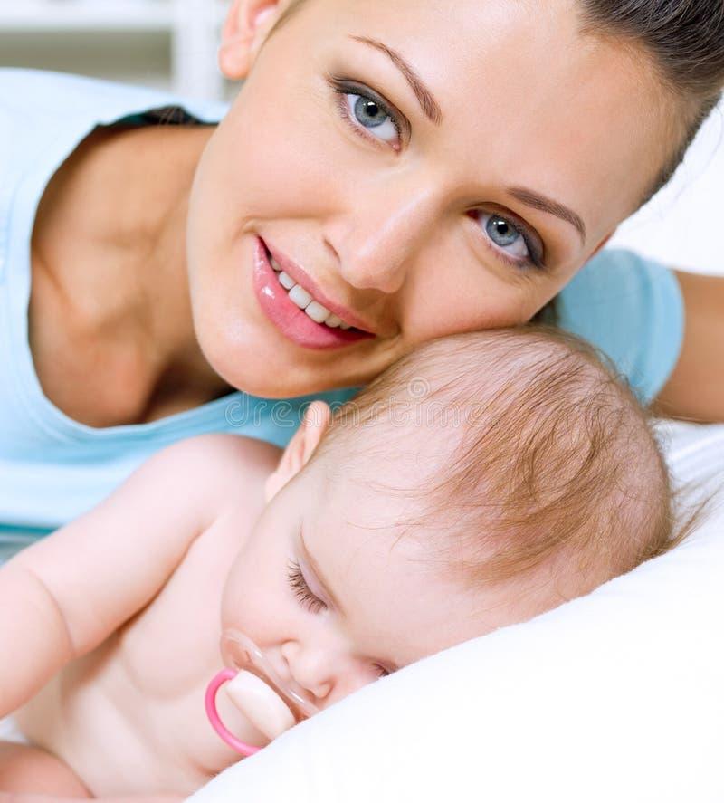 lycklig moder nära nyfött sova barn fotografering för bildbyråer