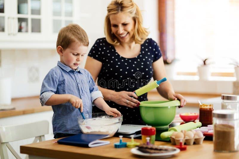 Lycklig moder och barn i kök arkivbild