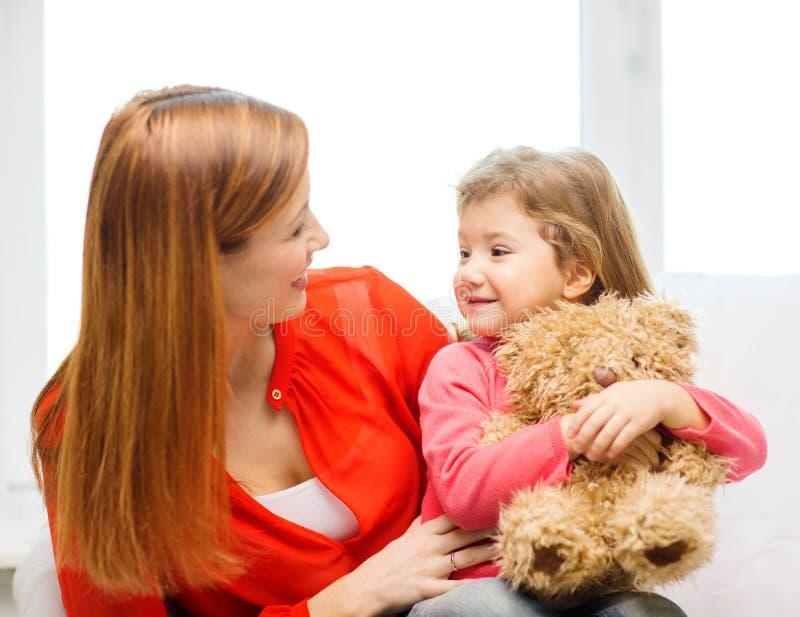 Lycklig moder och barn med nallebjörnen hemma royaltyfri bild