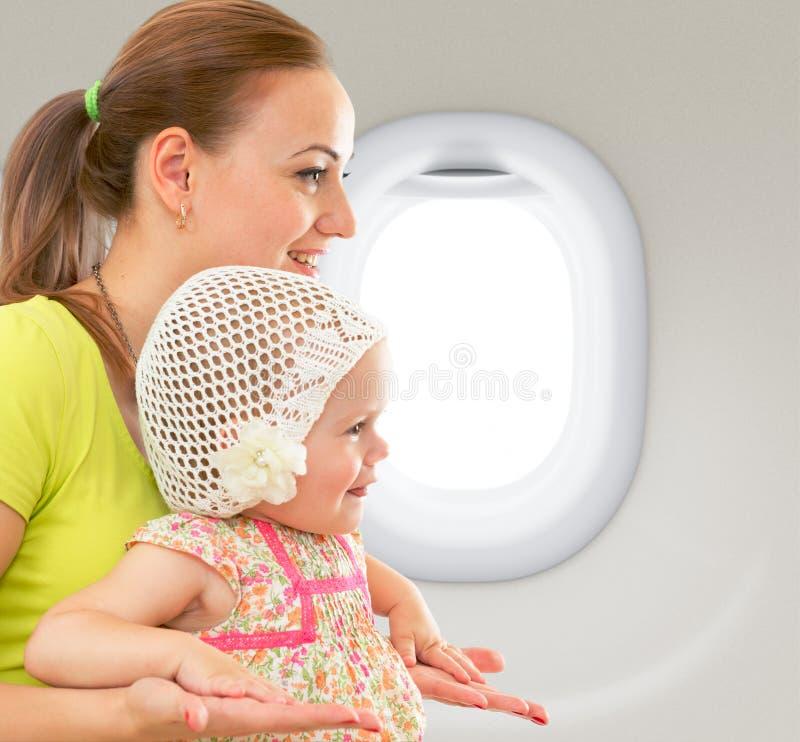 Lycklig moder och barn som tillsammans sitter i flygplankabin arkivbild