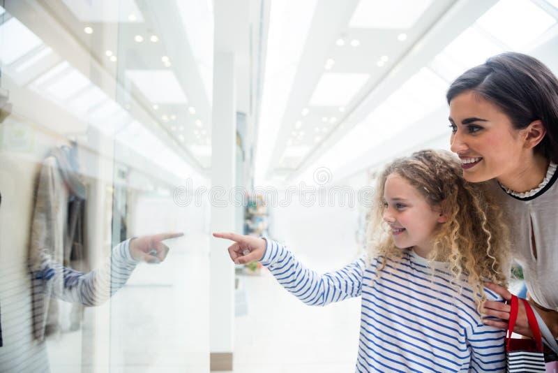 Lycklig moder och dotter i shoppinggalleria fotografering för bildbyråer