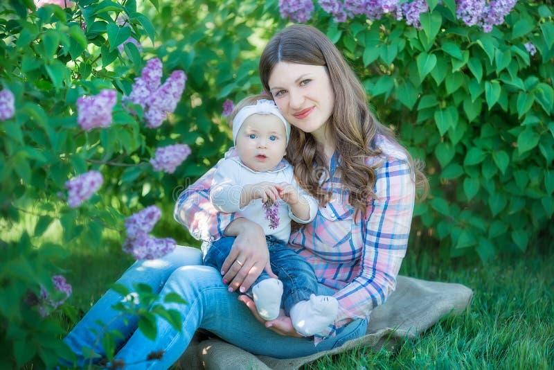 Lycklig moder och dotter med gröna äpplen i trädgården av blommande lilor royaltyfri foto