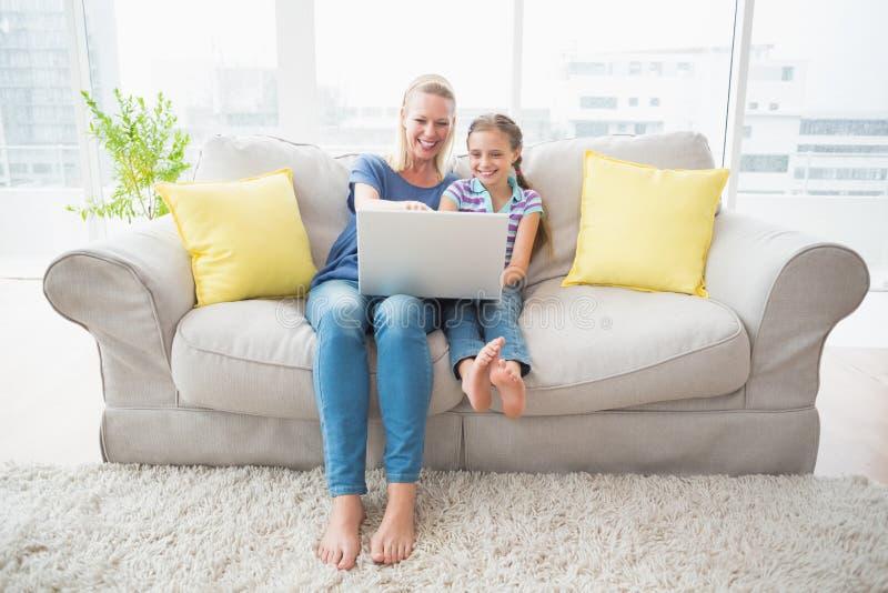 Lycklig moder och dotter som använder bärbara datorn på soffan arkivbild