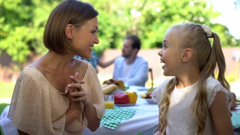 Lycklig moder och dotter som delar hemligheter på trädgård av stugan, flickasamtal fotografering för bildbyråer