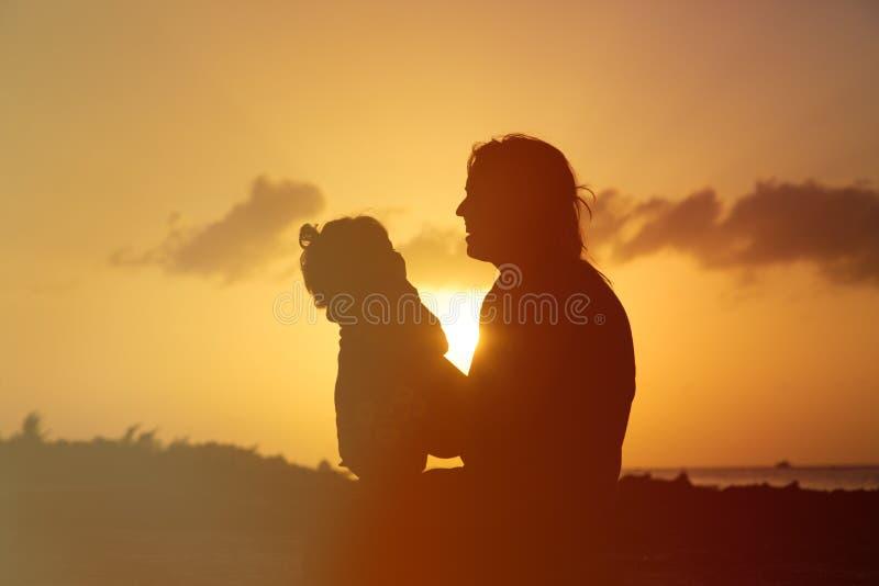 Lycklig moder och dotter som har gyckel på solnedgången royaltyfri bild