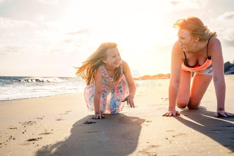 Lycklig moder och dotter som har gyckel på stranden i semester - mamma som spelar med hennes unge under deras ferier arkivfoton