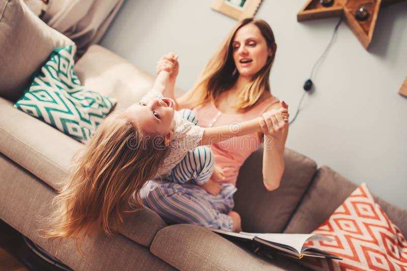 Lycklig moder och dotter som har roligt hemma på soffan arkivfoton
