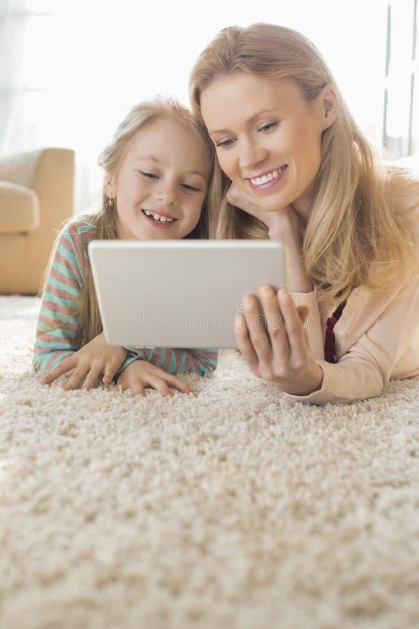 Lycklig moder och dotter som hemma använder den digitala minnestavlan på golv arkivbilder