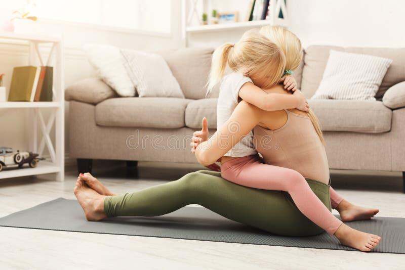 Lycklig moder och dotter som kramar medan hem- yogagrupp royaltyfri foto