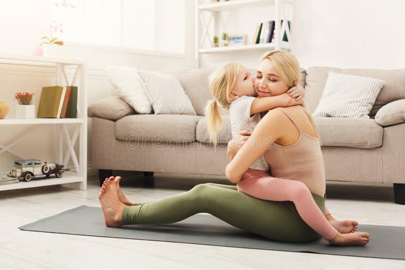 Lycklig moder och dotter som kramar medan hem- yogagrupp arkivfoto