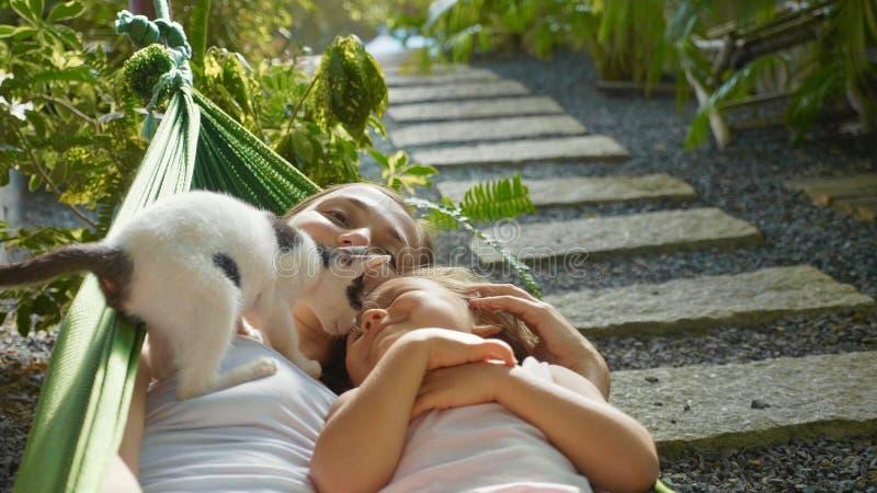 Lycklig moder och dotter som tillsammans kopplar av i en hängmatta på trädgården i sommardag arkivfoton
