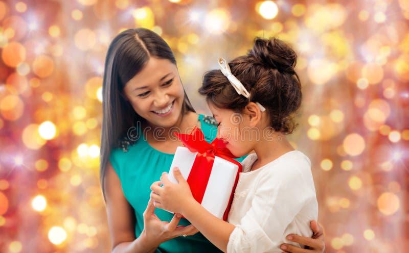 Lycklig moder och flicka med gåvaasken över ljus arkivbilder