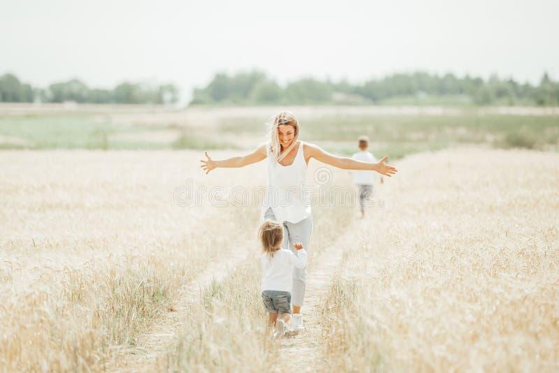 Lycklig moder och hennes barn som tillsammans spenderar tid i soligt fält arkivbild