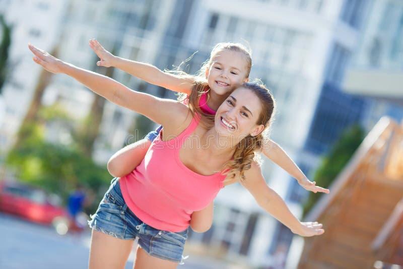 Lycklig moder och hennes dotter som utomhus spelar fotografering för bildbyråer