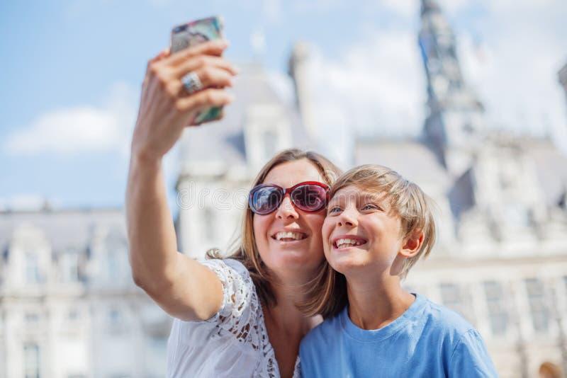 Lycklig moder och hennes son som g?r selfie n?ra Hotell de Ville i Paris Turister som tycker om deras semester i Frankrike royaltyfria foton